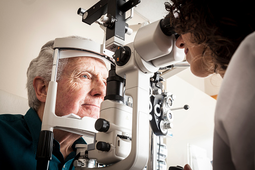 A picture containing person, person, microscope Description automatically generated